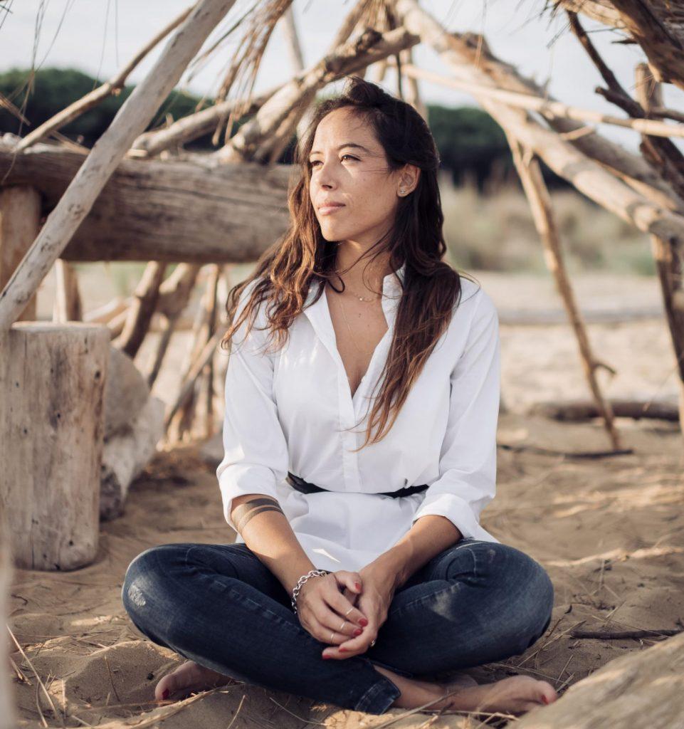 Arianna Reguzzoni Life Coach seduta con le gambe incrociate sulla sabbia all'interno di una struttura fatta di pezzi di legno trovati sulla spiaggia. Lo sguardo è rivolto sul lato verso la luce che arriva dal sole.
