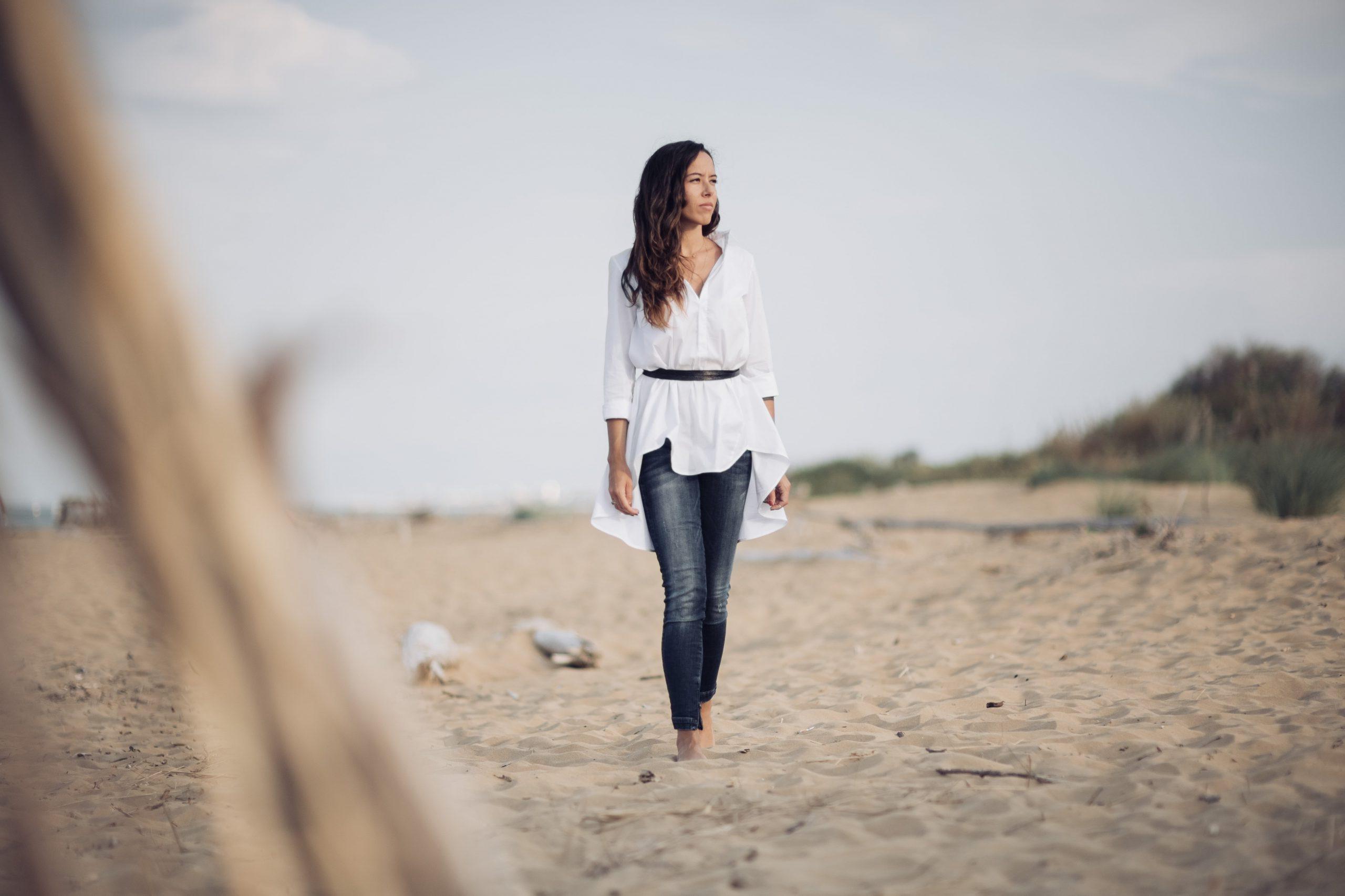 L'immagine rappresenta Arianna Reguzzoni Life Coach a figura intera che cammina sulla spiaggia guardando verso il mare. Indossa una camicia bianca lunga con una cintura nera in vita e jeans scuri.