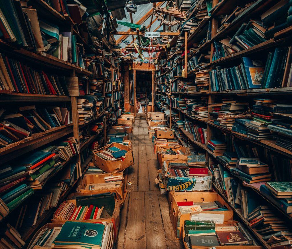 Stanza adibita a libreria disordinata.