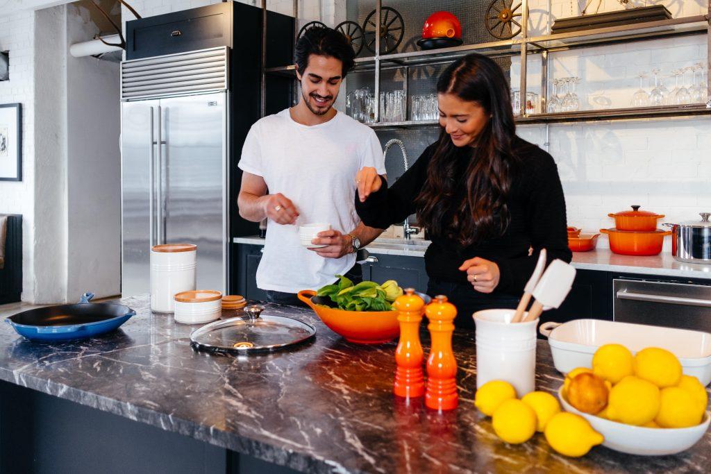 coppia in cucina, lui aspetta le indicazioni di lei mentre prepara un piatto