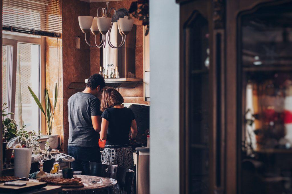 coppia di spalle in cucina che prepara insieme qualcosa