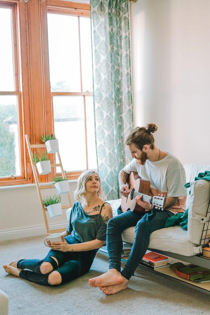 ragazzo seduto sul divano suona la chitarra, lei seduta sul tappeto lo osserva